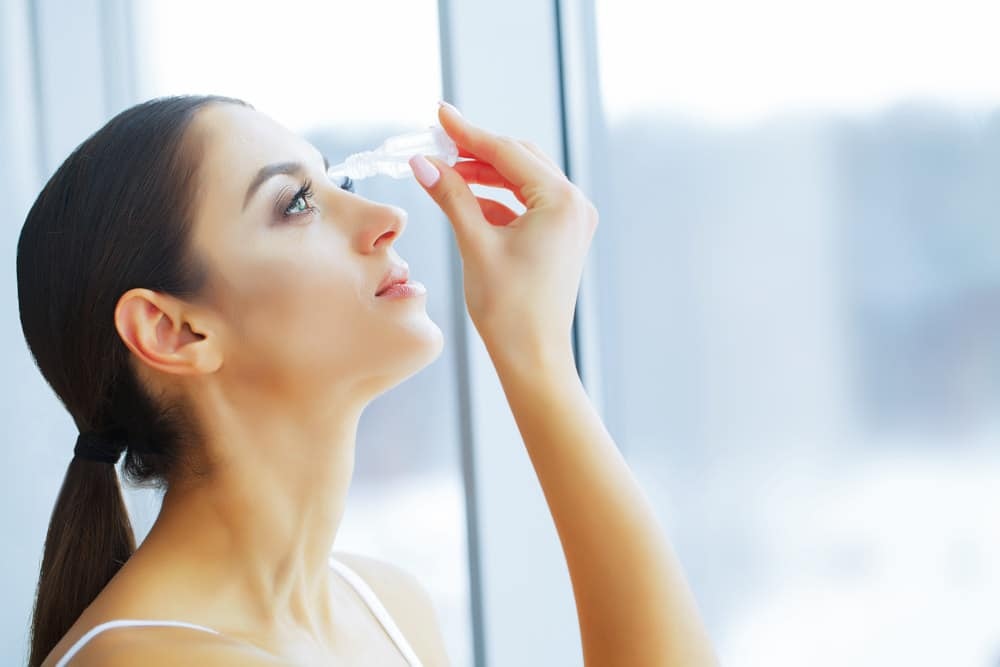 Women has a drops for allergic reactions to eyelash extensions.