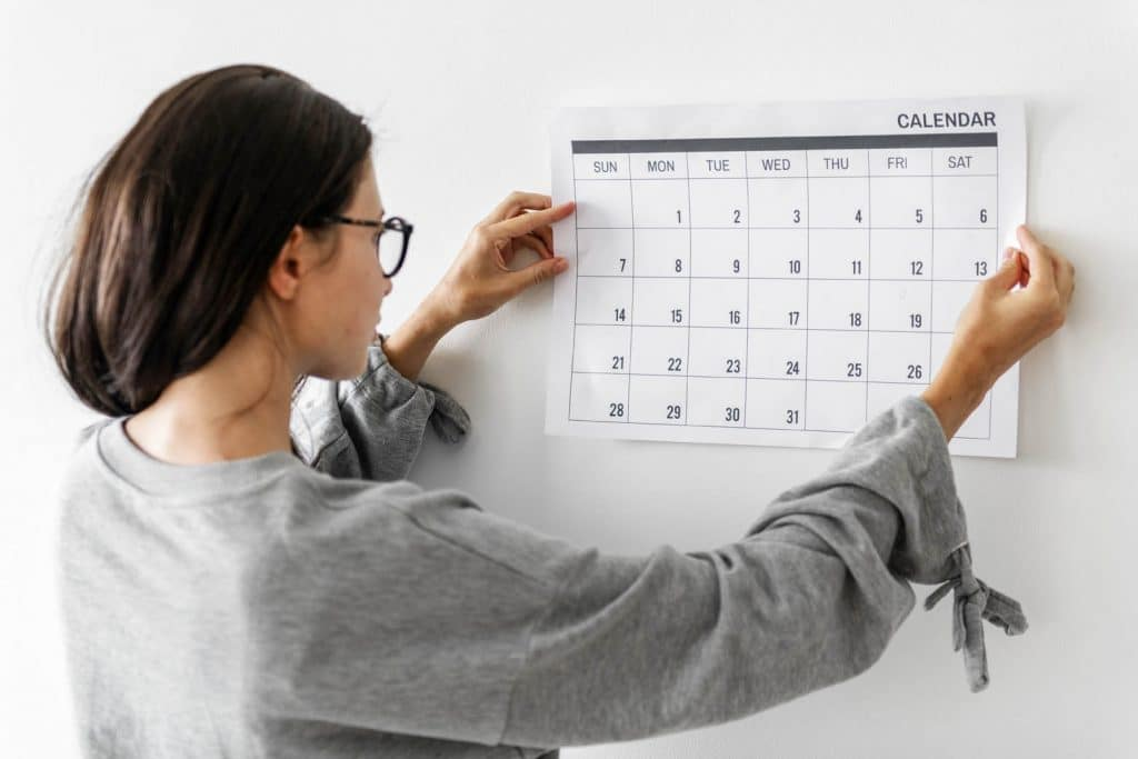 How to efficiently manage your time when running your lash business. Women checking the calendar .